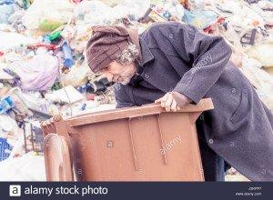 les-sans-abri-fouille-dans-la-poubelle-de-lenfouissement-j2kpp7